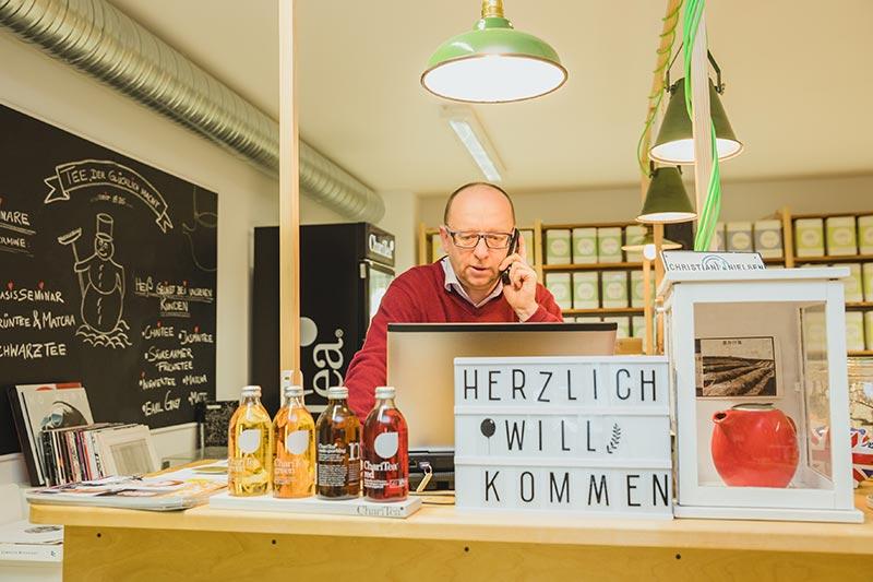 Alexander Poetsch telefoniert im Teeladen Evas Teeplantage mit seinen Kunden